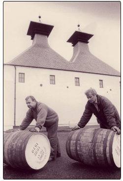 Two men pushing barrels at the Ardbeg Distillery on Islay