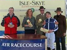 Iain Weir, Marketing Director Ian Macleod Distillers Ltd. presents Harriet's Girl winning team of the 16 September Isle of Skye Blended Scotch Whisky Handicap Stakes with bottles of Isle of Skye 8 Years Old Scotch. (Left to right: Iain Weir, Marketing Director Ian Macleod Distillers Ltd., Trainer Mrs K Burke, Owners Mr & Mrs Ray Bailey and winning jockey, Andrew Elliott.)