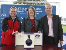 Iain Weir, Marketing Director, Ian Macleod Distillers Ltd. presents a rare bottle of Isle of Skye 21 Year Old to competition winner, Nigel Young and his partner.
